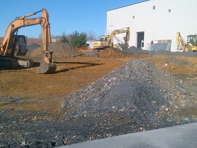 Excavating old asphalt and concrete at site.